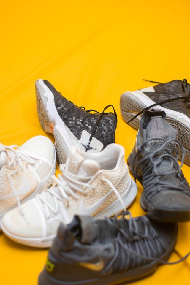 Diverse paia di scarpe su sfondo giallo